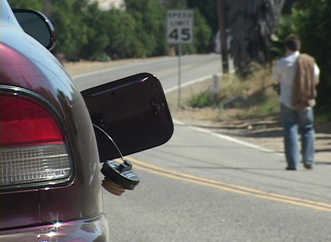 A man hitchhikes down a highway after his car runs out of gas Footage