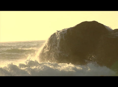 Waves crash against a large boulder in the ocean Stock Video Footage
