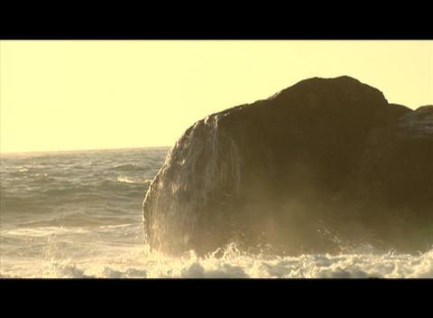 Waves crash against a large boulder in the ocean Footage