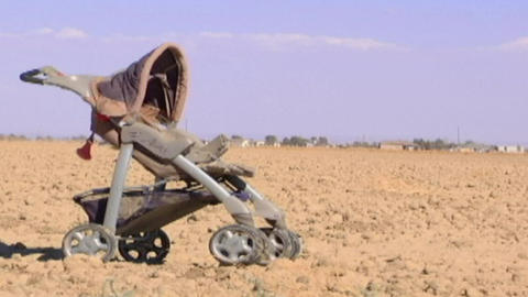A child's baby carriage sits in a lonely dirt field Stock Video Footage