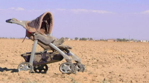 A child's baby carriage sits in a lonely dirt field Footage