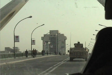 POV from a U S army convoy moving under the victory arch in central Baghdad during the Iraq War Footage
