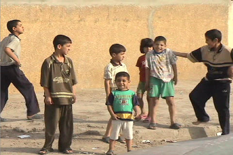 Kids play and jostle while standing on a street in Baghdad Iraq Footage