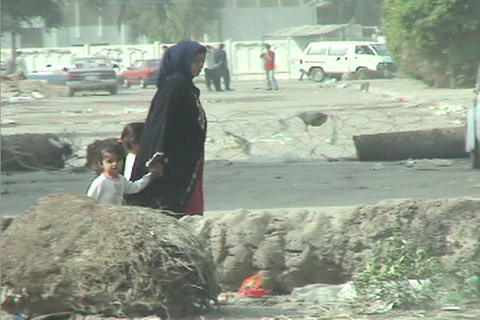 A veiled woman leads her children through the streets of... Stock Video Footage