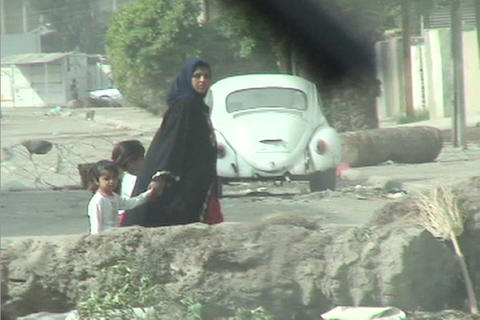A veiled woman leads her children through the streets of Baghdad during the Iraq war Footage