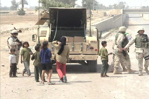 Small children interact with American soldiers along a... Stock Video Footage