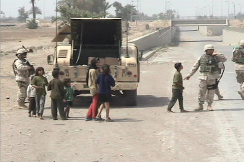 Small children interact with American soldiers along a road in Iraq Footage