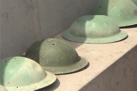 American soldiers helmets sit in a row along an army... Stock Video Footage