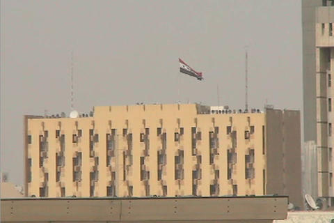 The Iraqi flag flies high above a public building in downtown Baghdad Iraq Footage