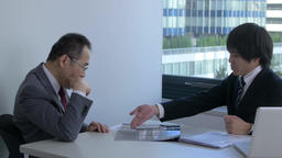Japanese businesspeople discussing in a modern office Footage