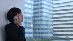Young Japanese businessman on the phone in a modern office Footage