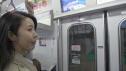 Japanese young woman boarding metro train downtown Tokyo Footage