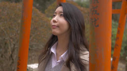 Slow motion footage of Japanese young woman walking through red Torii gates at a Footage