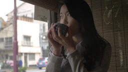Japanese young woman drinking green tea at a traditional restaurant downtown Tok Footage