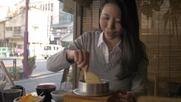 Japanese young woman eating at a traditional restaurant downtown Tokyo Footage