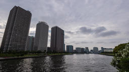 Time-lapse panning footage of cloudy sky over Tokyo cityscape before sunset, Tok Footage