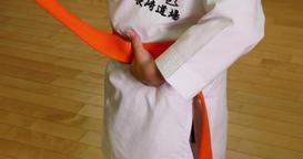 Japanese kid in karate uniform putting belt on in a gym Footage