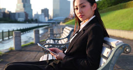 Attractive young Japanese woman in formal clothes using tablet by a river downto Bild
