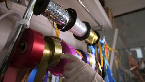 woman takes shiny pink ribbon from metal rack in floral shop Acción en vivo