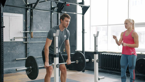 Young man training with female instructor in gym lifting barbell wearing trendy Live Action