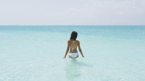 Bathing and swimming beach vacation woman walking in turquoise ocean Live Action