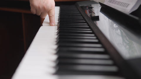 Electronic piano. Fingers press the piano keys. Children's hands on the piano keyboard Live Action