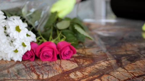 woman florist wraps gentle roses with transparent foil Acción en vivo