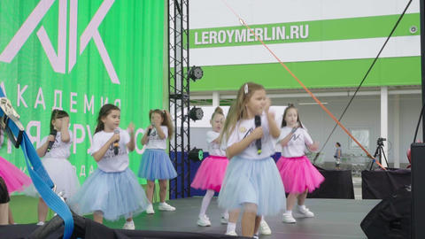 girls in bright skirts sing and dance on stage at concert Acción en vivo