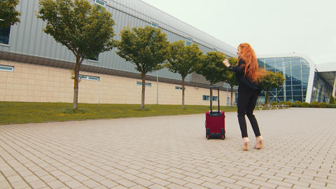 Happy young woman dancing near luggage suitcase on airport terminal background Live Action