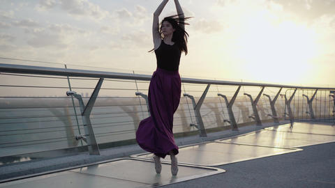 Elegant Caucasian ballerina spinning on tiptoes on bridge in the morning. Wide Live Action