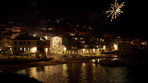 Fireworks in the beautiful coastal village at night. View of a small Acción en vivo