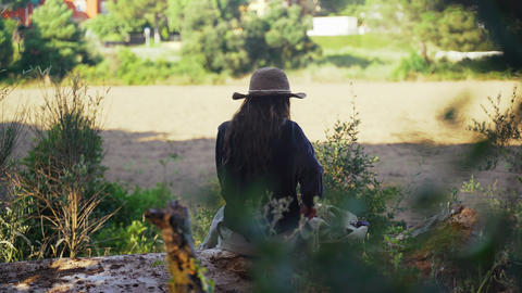 A young woman rest in the forest. A girl in a black shirt and a straw hat sits Acción en vivo