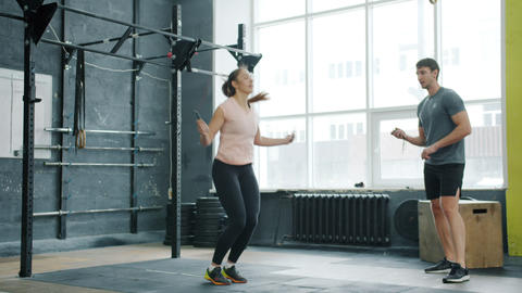 Active young woman jumping with skipping rope training with male trainer in gym Live Action