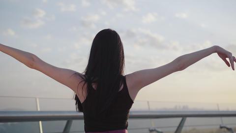 Back view of Caucasian ballerina raising hands up at summer sunrise. Brunette Live Action