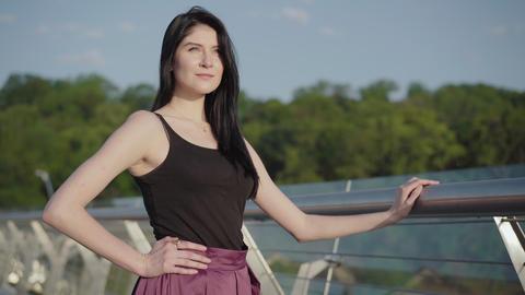 Portrait of confident beautiful Caucasian woman standing on bridge on sunrise Live Action