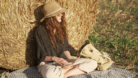 A young woman chill in the field. A girl in a black shirt and a straw hat Acción en vivo