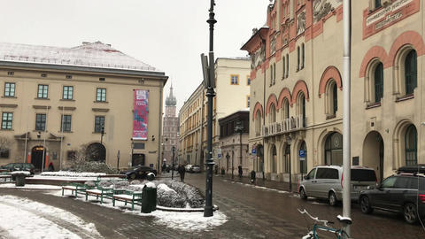 Krakow, Poland, A busy city street with cars parked on the side of a building Live Action