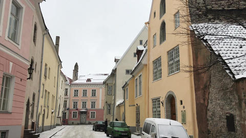 Tallinn, Estonia, A narrow city street with cars parked on the side of a Live Action