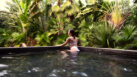 Handsome young caucasian woman in swimming pool tropical park in asia, bali Live Action
