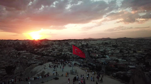 Sunset Over Cappadocia and Goreme City. Aerial of Viewpoint With Turkish Flag Live Action