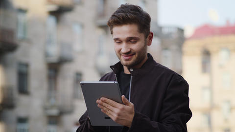 Happy guy reading message on tablet outside. Smiling man using device on street Acción en vivo