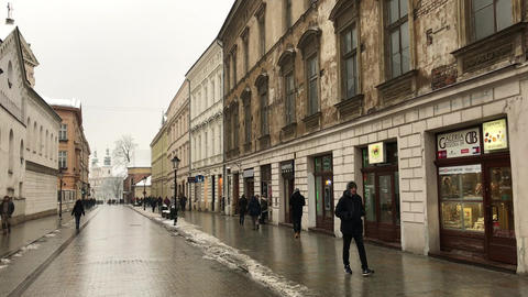 Krakow, Poland, A person walking down a street next to a building Live Action