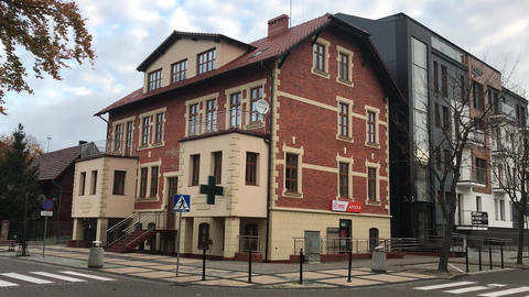 Ustka, Poland, A large brick building with a store on the corner of a street Live Action
