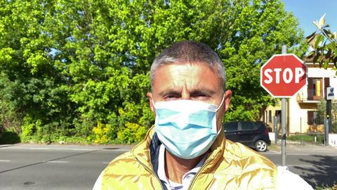 Man wearing mask walking outdoor in coronavirus ourbreak, slow motion Live Action