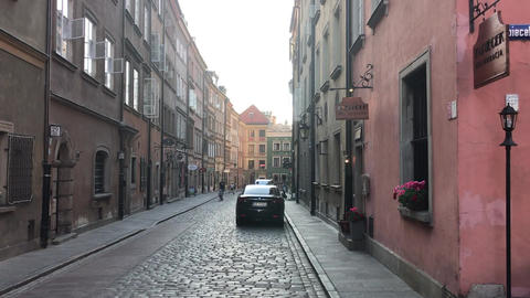 Warszawa, Poland, A narrow city street with cars parked on the side of a Live Action