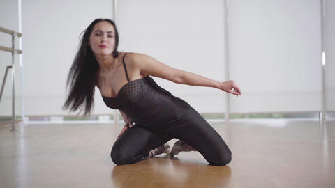 Flexible young woman sitting on the floor in gym and stretching. Portrait of Live Action