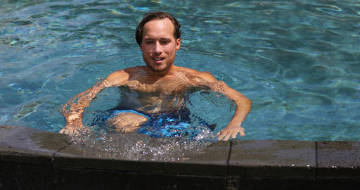 Man enjoying swimming pool resort vacation holidays Live Action