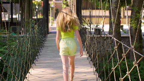 Rear view of girl walking on rope bridge at summertime GIF