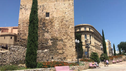 Tarragona, Spain, A castle with a clock tower in front of a brick building Live Action
