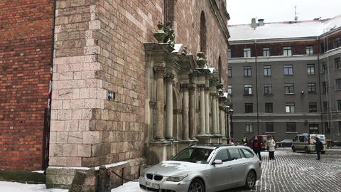 Riga, Latvia, A large brick building with a car parked on a city street Live Action